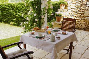 Petit déjeuner servi sur la terrasse avec vue sur la piscine et le parc de deux hectares.